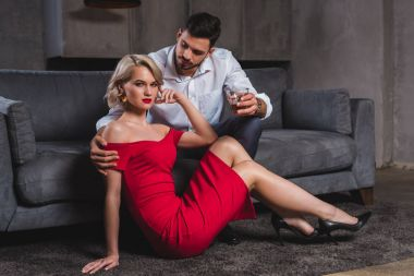 handsome man holding glass of whisky and looking at seductive young woman in red dress