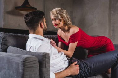 sexy young couple in fashionable clothes looking at each other in foreplay