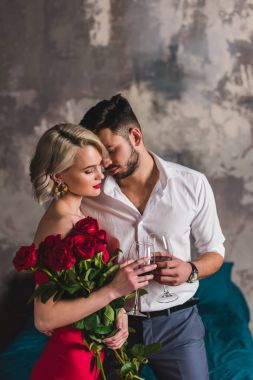 seductive young woman holding beautiful roses and drinking wine with handsome boyfriend
