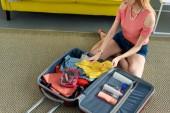 oříznutý pohled dívka sedí na podlaze a balení zavazadel pro cestování