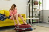 mladá žena balení cestovní tašku pro cestu