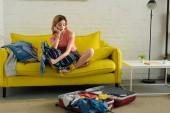 zamyšlená dívka balení oblečení do kufru pro cestování
