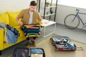 pohledný mladý muž balení oblečení v pytlích o cestování na dovolenou