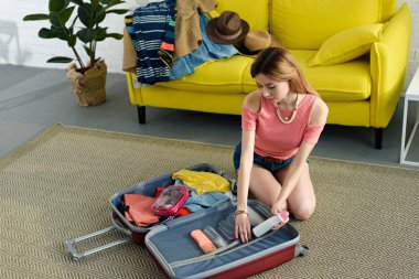 beautiful girl packing suitcase for travel on floor