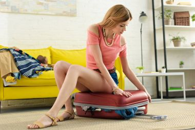 beautiful girl packing suitcase while sitting on it at home
