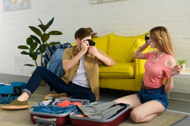 man taking photo of girlfriend in snorkeling mask at home