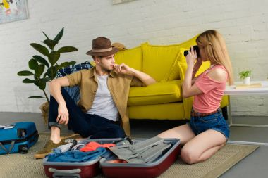 Young girl taking photo of boyfriend in hat while packing suitcase stock vector