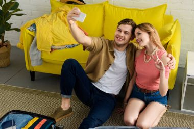 young couple taking selfie on smartphone while preparing for a vacation
