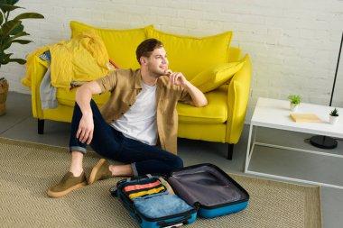 handsome dreamy man sitting on floor near travel bag