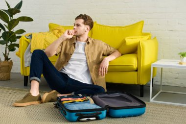 handsome pensive man sitting on floor near sofa with travel bag