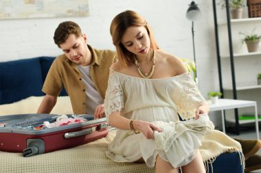pregnant woman and husband preparing suitcase for hospital