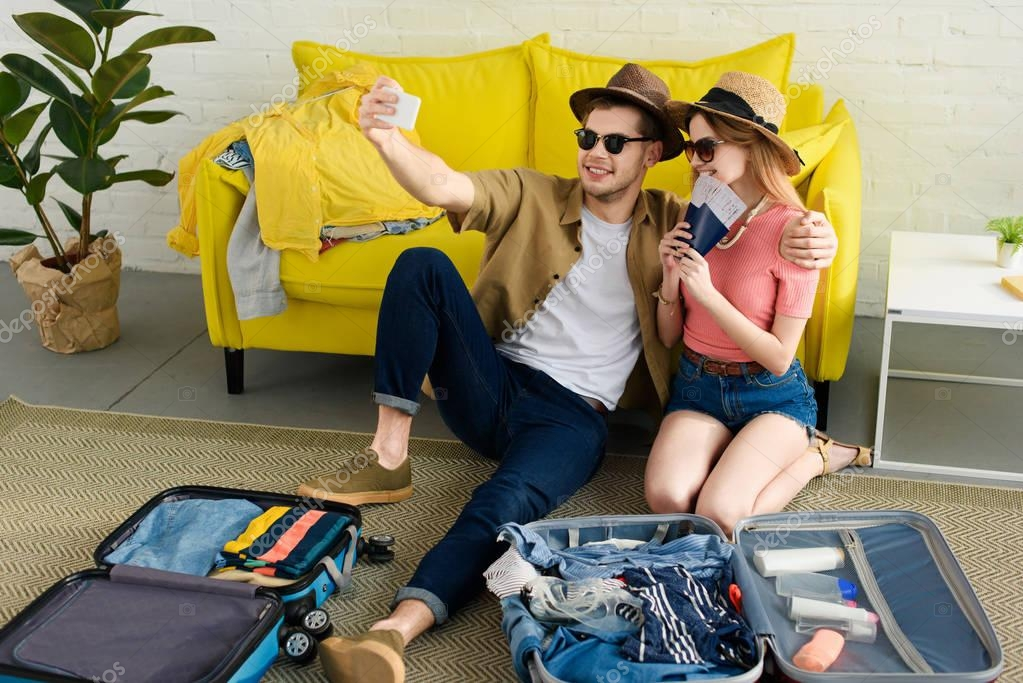 Beautiful couple taking selfie on smartphone while packing suitcases for vacation