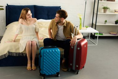 happy couple with suitcases ready for vacation sitting on bed