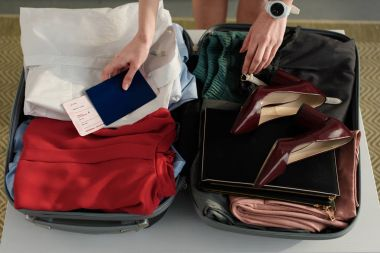 cropped view of woman packing clothes in suitcase for business trip and holding passport with air ticket