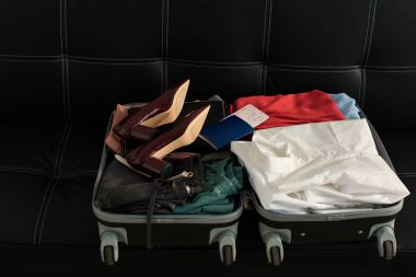 opened travel bag with passport, clothes and heels on sofa
