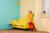 Photo pensive young woman in retro clothing sitting on yellow sofa at colorful apartment, doll house concept