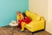 Fotografie ženy sedí na žluté pohovce s akvarijních ryb na konferenční stolek v bytě barevné, panenky dům koncept v retro stylu
