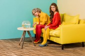 Photo retro styled women sitting on yellow sofa with aquarium fish on coffee table at colorful apartment, doll house concept