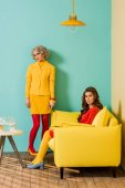 Photo young retro styled women in colorful apartment with yellow sofa and aquarium fish, doll house concept