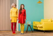 Photo young retro styled women standing in colorful room, doll house concept