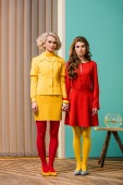 Photo women in bright retro styled clothing holding hands at colorful apartment, doll house concept