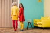 Fotografie zadní pohled na ženy v jasných retro stylem oblečení, drželi se za ruce v bytě barevné, panenky dům koncept