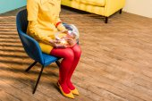 Photo partial view of woman in retro clothing with golden fish in aquarium sitting on chair at colorful apartment, doll house concept