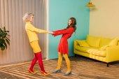 Fotografie boční pohled docela s úsměvem ženy v retro oblečení, drželi se za ruce na barevné byt, panenka dům koncept