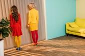 Fotografie Rückansicht der Frauen in helle Kleidung Stand am Fenster in bunten Wohnung, Puppe-Haus-Konzept
