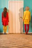 Fotografie zadní pohled na retro stylizovaný žen stojí u dveří v bytě barevné, panenky dům koncept