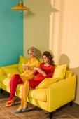Fotografie retro stylu ženy pomocí smartphone při odpočinku na pohovce žluté, panenka dům koncept
