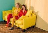 Fotografie ženy mluví na smartphone na žluté pohovce, panenka dům koncept v retro stylu