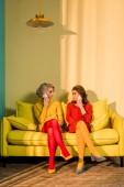 Fotografia donne che comunicano su smartphone sul divano giallo, concetto di casa di bambola in stile retrò