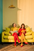 Photo women in retro clothing reading books sitting on yellow sofa at bright apartment, doll house concept
