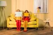 Photo obscured view of women in retro clothing with books sitting on yellow sofa at bright apartment, doll house concept