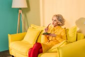 Photo retro styled woman with broccoli on plate and chili pepper in hand resting on sofa at bright apartment, doll house concept