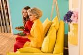 Fotografie krásné ženy v retro oblečení se zeleninou na talířích sedí na měděně na barevné pokoje, panenka dům koncept