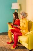 Fotografia belle donne in abbigliamento retrò con le verdure su piatti seduti sul divano giallo di camera luminosa, concetto di casa di bambola