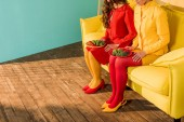 oříznutý obraz retro stylizovaný dívek v barevné šaty sedí s deskami z brokolice doma