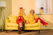 Fotografia retrò in stile belle ragazze in abiti rossi e gialli sul sofà a casa