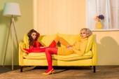 Fotografia retrò in stile belle ragazze in abiti colorati sdraiata sul divano e rivolto a casa