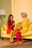 Fotografia retrò in stile belle ragazze in abiti colorati che giocano roccia carta forbici gioco sul sofà a casa