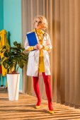 Fotografie beautiful retro styled doctor in colorful dress holding clipboard and looking away in clinic