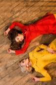 Fotografia vista superiore di belle ragazze in stile retrò in abiti colorati che si trovano del pavimento a casa