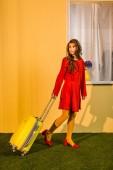 krásné retro stylu ženy v červených šatech chodit s kufrem doma, cestování koncepce
