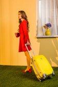 boční pohled na krásné retro stylizovaný ženy v červených šatech stojící odpadkový pytel doma, cestování koncepce