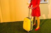 Fotografie zugeschnittenes Bild retro gestylten Frau im roten Kleid mit Reisetasche zu Hause stehen