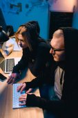 Photo confident couple of hackers working on malware together in dark room