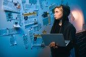 Fotografie Hackerin mit Laptop steht vor Wand mit Zeitungsausschnitten