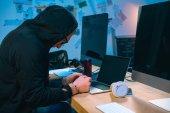 pouta hacker v hoodie před přenosného počítače na pracovišti